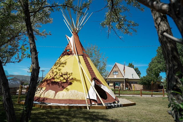 A teepee with a buck on it is located right in front of a building at the Flaming Gorge KOA