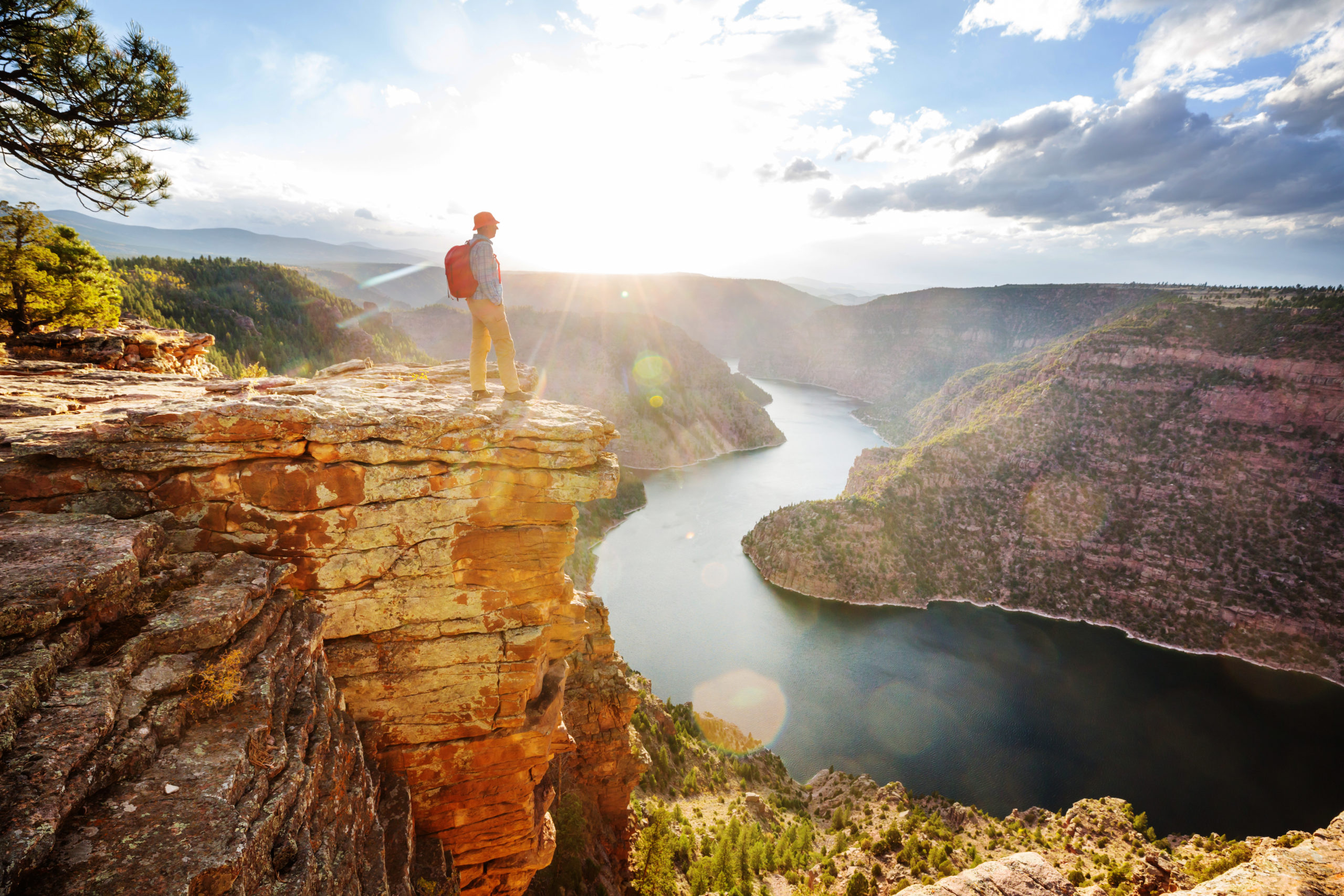 a man stands on a cliff overlooking Flaming Gorge Reservoir