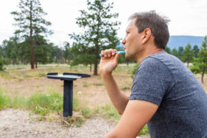 man brushing teeth while camping in Ashley National Forest