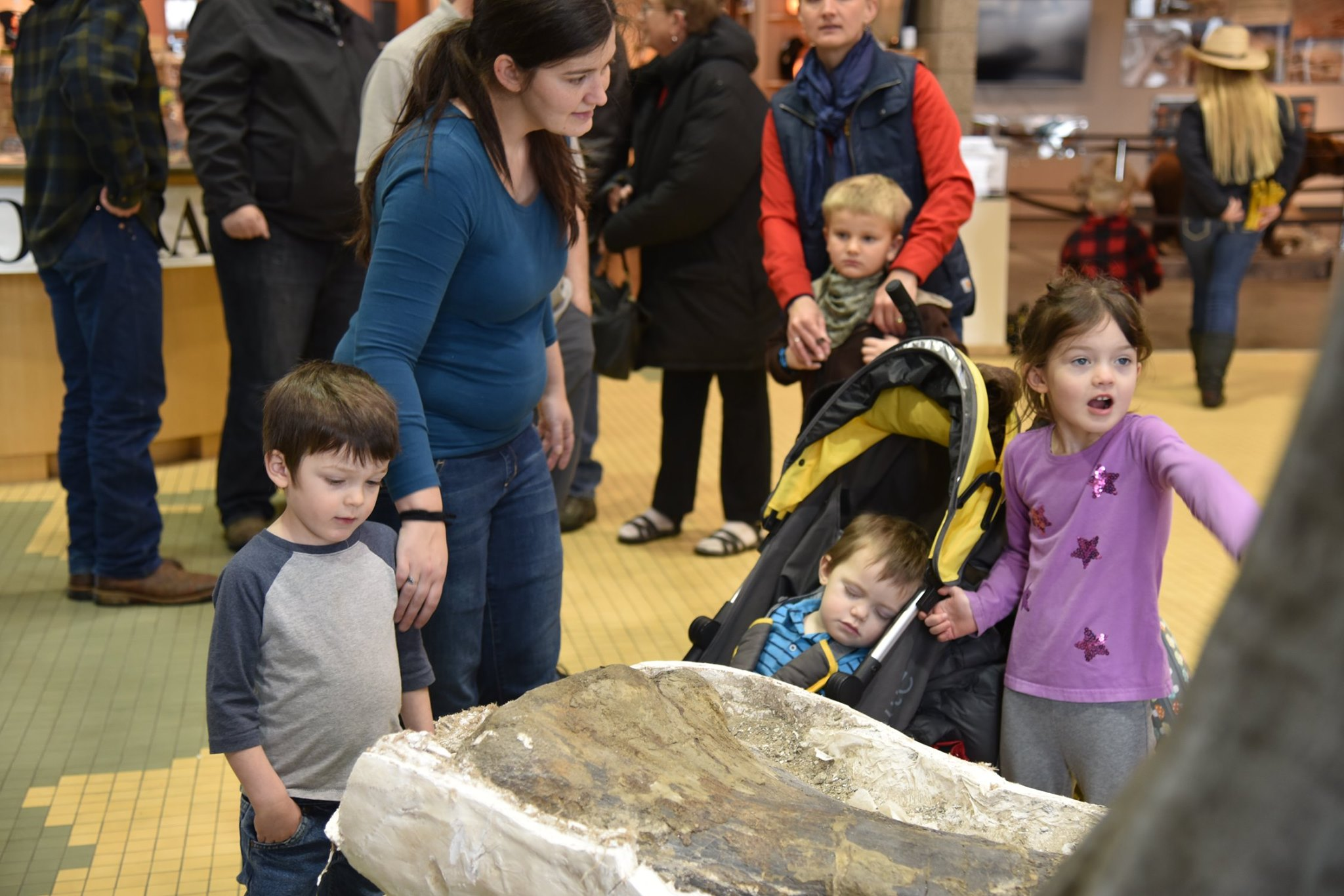 a family including children look at a dinosaur fossil display in Utah