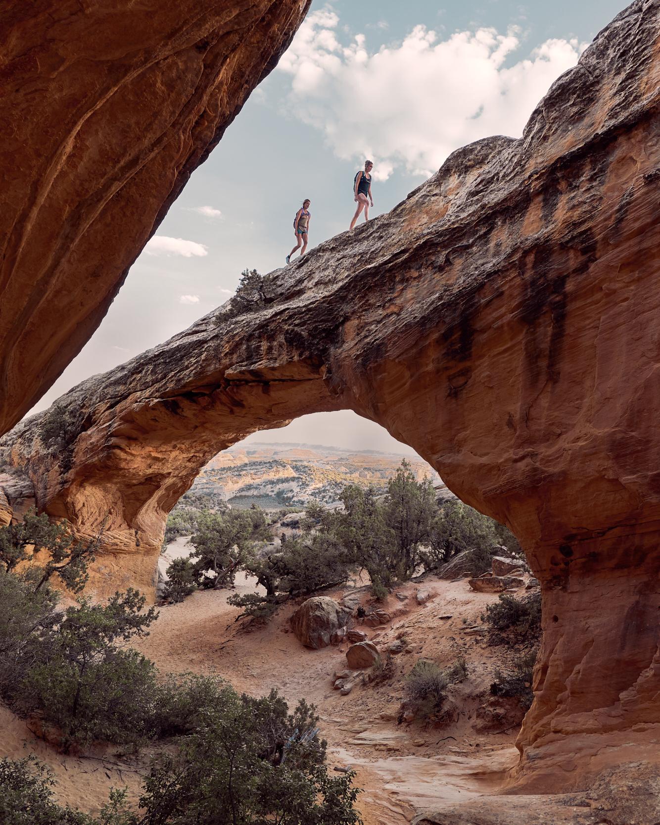 Hikers Walk Along the top of Moonshine Arch in Vernal utah