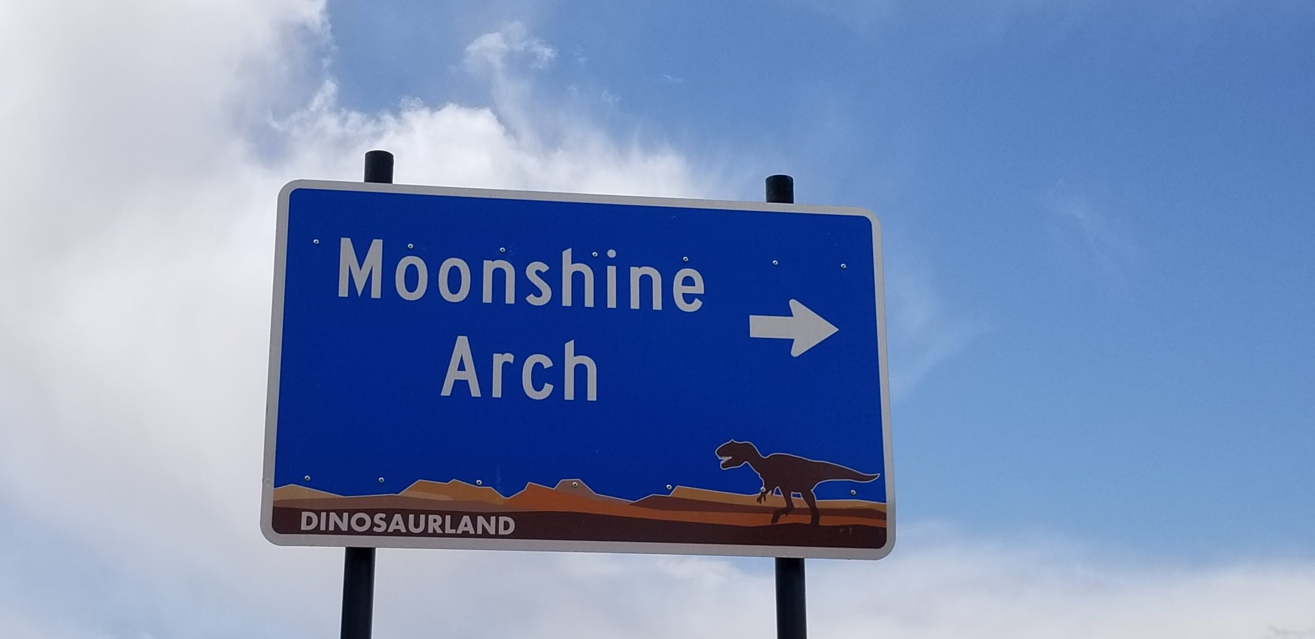 Blue Moonshine Arch Sign with arrow pointing towards the hike